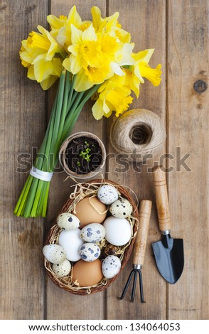Spring symbols - daffodils, basket with eggs and gardening tools on a wooden table