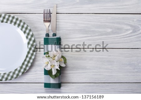 Spring table setting. Plate and cutlery decorated with flowers of apple on a wooden table. Top view.