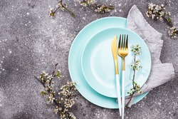 Spring table setting with blooming branch and trendy aqua menthe color plate