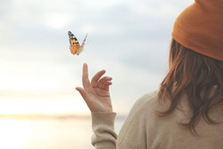 spring time, a butterfly leans delicately on a woman's hand