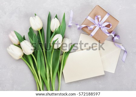 Spring tulip flowers, gift box and paper card on gray stone table from above in flat lay style. Greeting for Womens or Mothers Day.