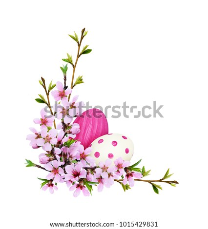 Spring twigs of peach flowers and early leaves with painted eggs in corner Easter arrangement isolated on white background #1015429831