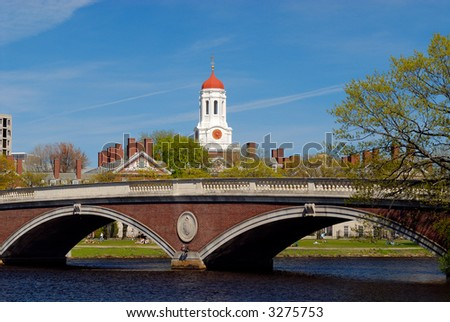 Spring view of Harvard University Dunster House's red dome and John W. Weeks Bridge in Cambridge, Massachusetts. Students relaxing on Charles River bank.
