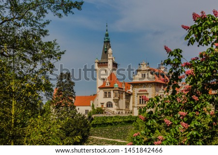 Spring view of romantic Pruhonice castle, Czech Republic, Europe, standing on hill in a park, sunny spring day with blue sky. Blooming chestnut tree in foreground. Leaves framing picture.