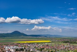 Spring view over Rasnov city, in Brasov county (Romania), with Codlea mountain in the background and with Cristian village in the far right
