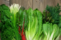 Spring vitamin set of various green leafy vegetables on rustic wooden table. Top view point.