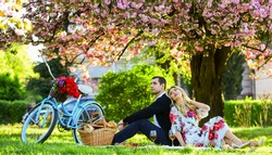 Spring weekend. Romantic picnic with wine. Give uncommon, unique gifts spontaneously. Happy loving couple relaxing in park with food. Enjoying their perfect date. Couple in love picnic date