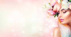 Spring Woman. Beauty Summer model girl with colorful flowers wreath and colorful hair. Flowers Hair Style. Beautiful Lady with Blooming flowers on her head. Nature Hairstyle. Holiday Fashion Makeup.