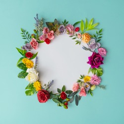 Spring wreath made of colorful flowers and leaves. Natural round frame layout with paper card. Flat lay.