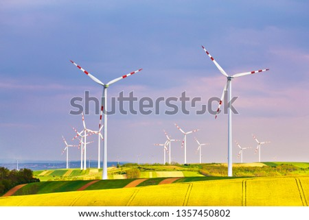 Spring yellow colza fields with wind power generators. Wind turbines park generating electricity. Green environment. Lower Austria near Poysdorf. #1357450802