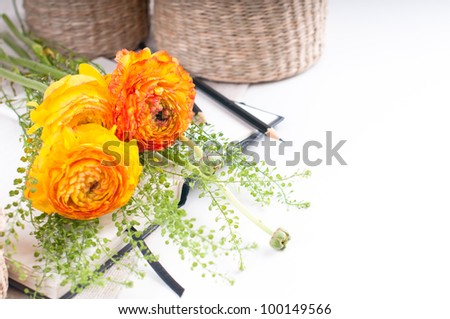 Spring yellow flowers, wicker baskets and a notebook on a white background