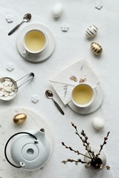 Springtime afternoon tea. Spring pussy willow flowers, white teapot and tea cup on table. Flat lay, off white textile tablecloth. Easter eggs, white ceramic cups and sugar hearts.