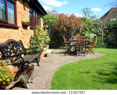 Springtime in an back garden in England with seating and Patio area