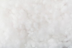 Springy clean white hollow fiber. Holofiber closeup texture. Non-woven synthetic textile