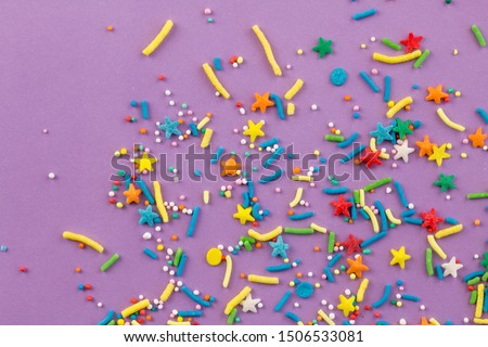 Sprinkle background with rainbow sprinkle shapes, stars, stripes, little balls on lilac background, close up top view photo