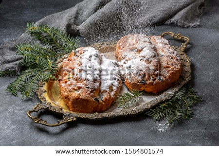 Sprinkled with powdered sugar on a homemade German Christmas Stollen in a metal tray and green fir branches on a textured dark background, selective focus.