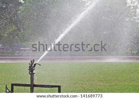 Sprinkler spraying water over lawn - stock photo