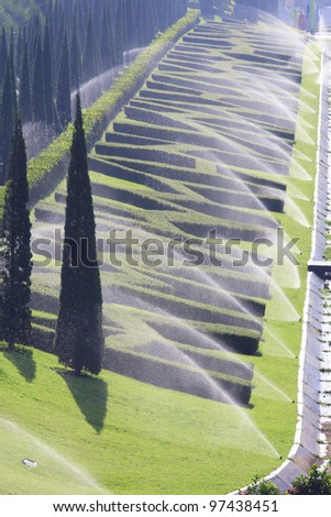 sprinkler system watering bush in park