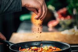 Sprinkling ground red chili pepper paprika over sliced vegetables, motion blur
