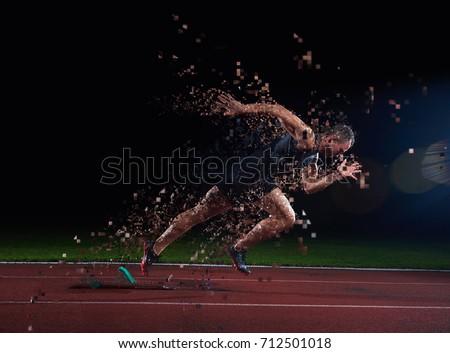 Sprinter leaving starting blocks on the running track. Explosive start.