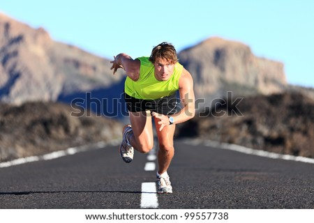 Sprinter. Man running on road at high speed in beautiful exotic mountain landscape. Male athlete runner in intense sprint during outdoor workout