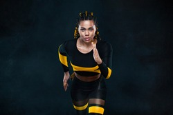 Sprinter run. Strong athletic woman running on black background wearing in the sportswear. Fitness and sport motivation. Runner concept.