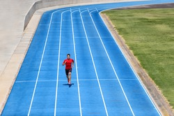 Sprinter runner athlete man sprinting on outdoor track and field running lanes at stadium. Sport and health active training on blue tracks.