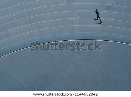 Sprinter running on athletic track. Top view of a sprinter running on race track in a stadium with shadow falling on the side. #1144632842