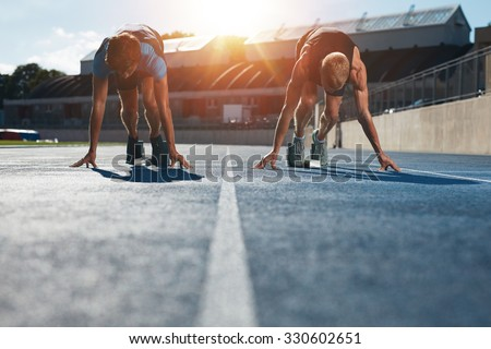 Sprinters at starting blocks ready for race . Athletes at starting position on athletics stadium race track with sun flare.