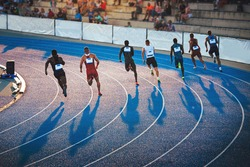Sprinters running on the athletics Track in sunset light. Shadows on the track, Sprint, Track and Field photo, original wallpaper for games in Japan, Tokyo. Athletics meeting on blue track