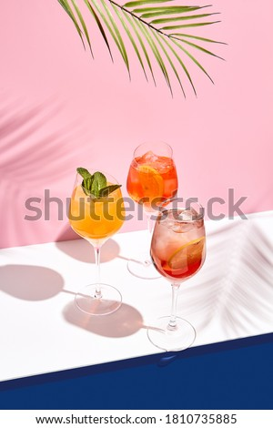 Spritz cocktail set on white table. Tropical palm leaf shadow. Summer cocktail group. Pink and classic blue background