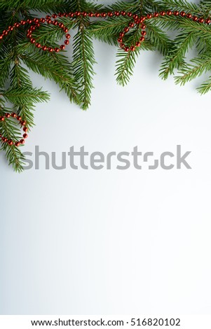 Spruce branches and red beads on a white background #516820102