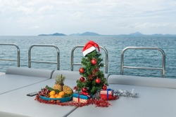 Spruce tree decorated with toys on a luxury yacht. Christmas in tropical countries. A plate with fresh fruits: tangerines, pineapples, grapes.