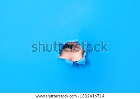 Spy concept. Kid's eye peeking through hole in paper. Spying through hole in blue paper. Spy eye looks through paper wall. Boy's eye is watching us through hole. Eye peering in sheet of paper hole.