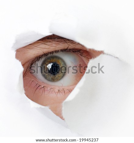 Spy eye peek through hole in paper - concept of espionage