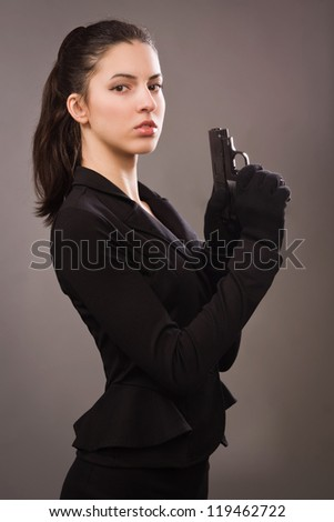 Spy girl in a black coat with gun