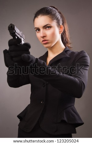 Spy girl in a black suit shoots a gun - stock photo