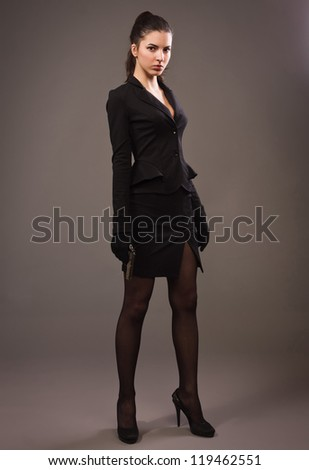 Spy girl in a black suit with gun - stock photo