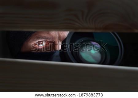 Spy Man. Peeping. Spying. Surveillance. Secret Information. Hidden Camera. Man hiding. Paparazzi. Stalker. Private Detective. Spy Camera. Spy Detective. Espionage. Privacy. Information. Investigation