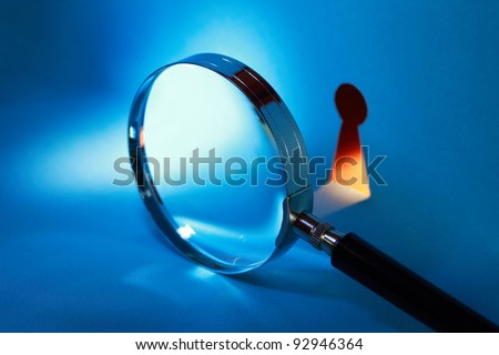 Spying concept. Magnifying glass near keyhole with beam of light