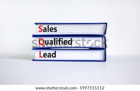 SQL sales qualified lead symbol. Books with words 'SQL sales qualified lead'. Beautiful white background. Business and SQL sales qualified lead concept. Copy space.