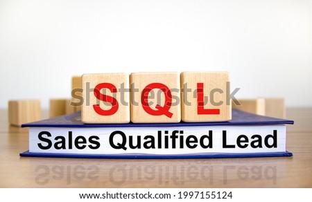 SQL sales qualified lead symbol. Wooden cubes on book with words 'SQL sales qualified lead'. White background. Business and SQL sales qualified lead concept. Copy space.