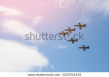 Squadron of air transport high in the sky makes a demonstration performance at the air show. A team of five sports aircraft against the blue sky. Pink sunset in the sky with a plane.
