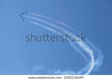 Squadron of air transport high in the sky makes a demonstration performance at the air show. Bottom view of the group of aircraft. Silhouette of the plane against the blue sky.