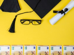 Square academic cap, diploma, glasses and money on yellow background with place for text in the middle, top view close-up.