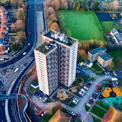 Square - aerial view of a highrise block of flats in Southampton in the United Kingdom on a sunny day. The appartments are on the edge of a roundabout. Houses and fields in the area.