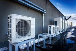 Square air-conditioning unit on the roof with a round fan. In the background gradually receding other units that are out of focus. On the right side light blue sky and commercial space.
