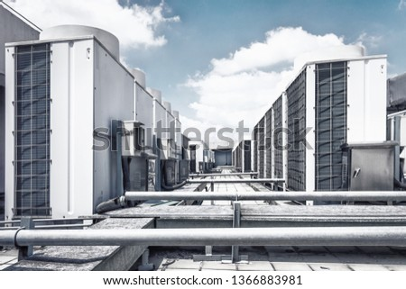 Square air-conditioning unit on the roof with a round fan. In the background gradually receding other units that are out of focus. On the right side light blue sky and commercial space. #1366883981