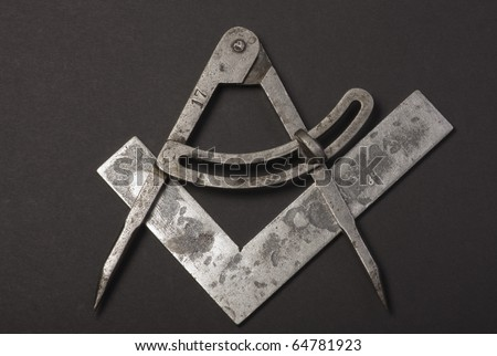 Square and Compasses on black background. Depicting the logo of Freemasons.
