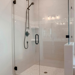 Square Bathroom shower stall with half glass enclosure adjacent to built in bathtub